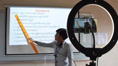 Ein Lehrer hält eine Unterrichtsstunde, die gefilmt und online übertragen wird
