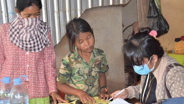 Eine PSE-Mitarbeiterin registriert Mutter und Tochter vor der Verteilung