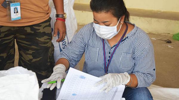 Eine PSE-Mitarbeiterin prüft die Listen für die Reisverteilung