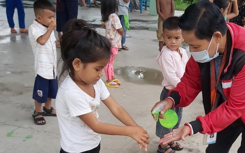 Un éducateur de PSE donne du gel hydroalcoolique a une petite fille pour qu'elle se lave les mains